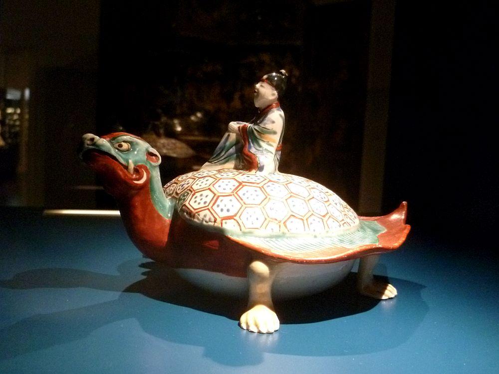 Eine Porzellanschildköte die Rot und Grün bemalt ist. Ein Reiter sitzt auf dem Schildkrötenpanzer. Er ist in einem blauen Kimono gekeildet.