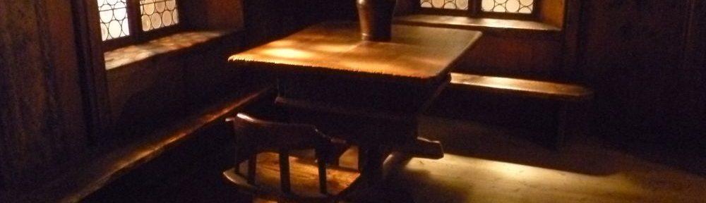 Eine Bauernstube aus dem 15. Jahrhundert. Die Stube ist sehr Düster und aus Holz gebaut, zusehen ist eine übereckverlaufende Sitzbank an der ein großer Tisch steht