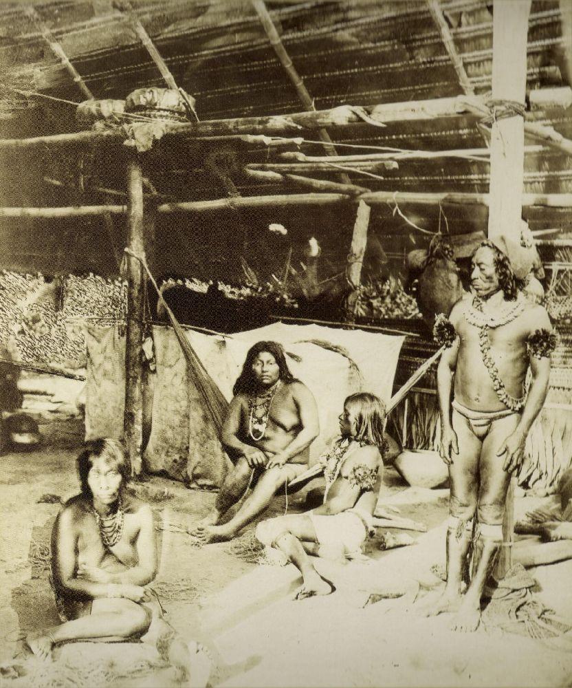 4 Tikuna in traditionelle Kleidung auf einem schwarz-weiß-Bild. Die Personen sind ein einem Haus. Eine Frau sitzt mit freiem Oberkörper in einer Hängematte, eine andere ebenso Oberkörperfrei an einem Feuer auf dem Boden. Ein Mann der einen Lendenschurz trägt sitzt ebenfalls auf dem Boden und unterhält sich mit der ersten Frau. Ein dritter, ebenfalls im Ledenschurz steht danben.