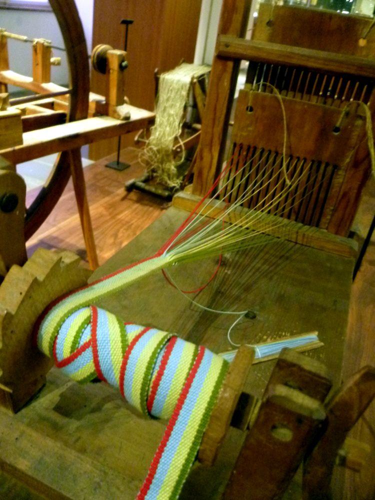 Ein bändchenwebstuhl aus Holz mit einem in vier Farben gewebten Bändchen