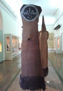 Eine Maske der Tikuna mit inem Ganzkörperkostüm. Durch den Hohen Holzkopf ist das Kostüm gut 2 m hoch. Der Kopf iat aus Holz, mit einem Runden Gesicht das Mit weisen Konturen gekennzichnet ist. Der rst der Kostüms besteht aus braunem Stoff.