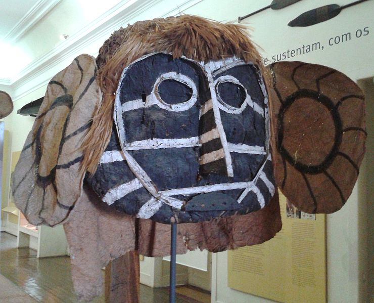 Eine Große Maske aus Holz und Leinenstoff. Das Gesicht ist aus Holz gefertiegt. Es ist schwarz und mir weißen streifen bemalt. Haare und Ohren bestehen aus braunem Stoff.