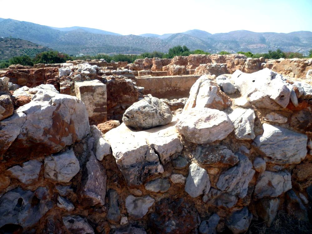 Eine Mauer aus hellem Bruchstein im Vordergrund, Ruinen aus rotem Stein im Hintergrund. Es wirkt wie ein Labyrinth.