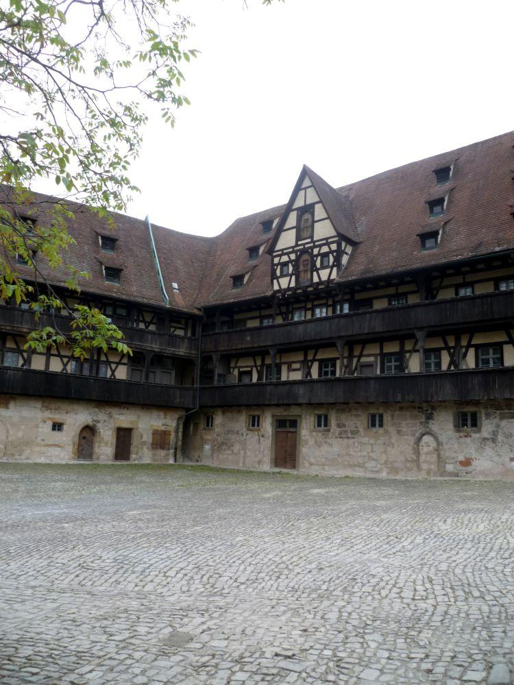 Die Alte Hofhaltung in Bamberg. Ein Altes gebäude mit einem Erdgeschoss, das aus graubraunem Stein gebaut ist, darüber befinden sich zwei Etagen aus gelben Fachwerk mit umlaufenden holzbalkonen. Das Dach zieht sich über drei stockwerke und ist rot gedeckt. Es ist vm innenhof aus Fotografiert mit dem Blick auf eine Ecke.