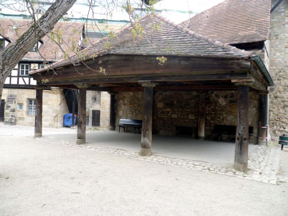 Ein an einen antiken Tempel erinnernder Bau 4 Holzsäulen tragen auf der Vorderseite das Dach, vorne links und rechts gibt es keine weiteren Mauern. Auf der rückseite befindet sich eine Braune steinmauer. Das Dach besteht aus dunklen schindeln, die auf einen Holzaufbau befestiegt sind. Es handelt sich um eine alte Hufschmiede.