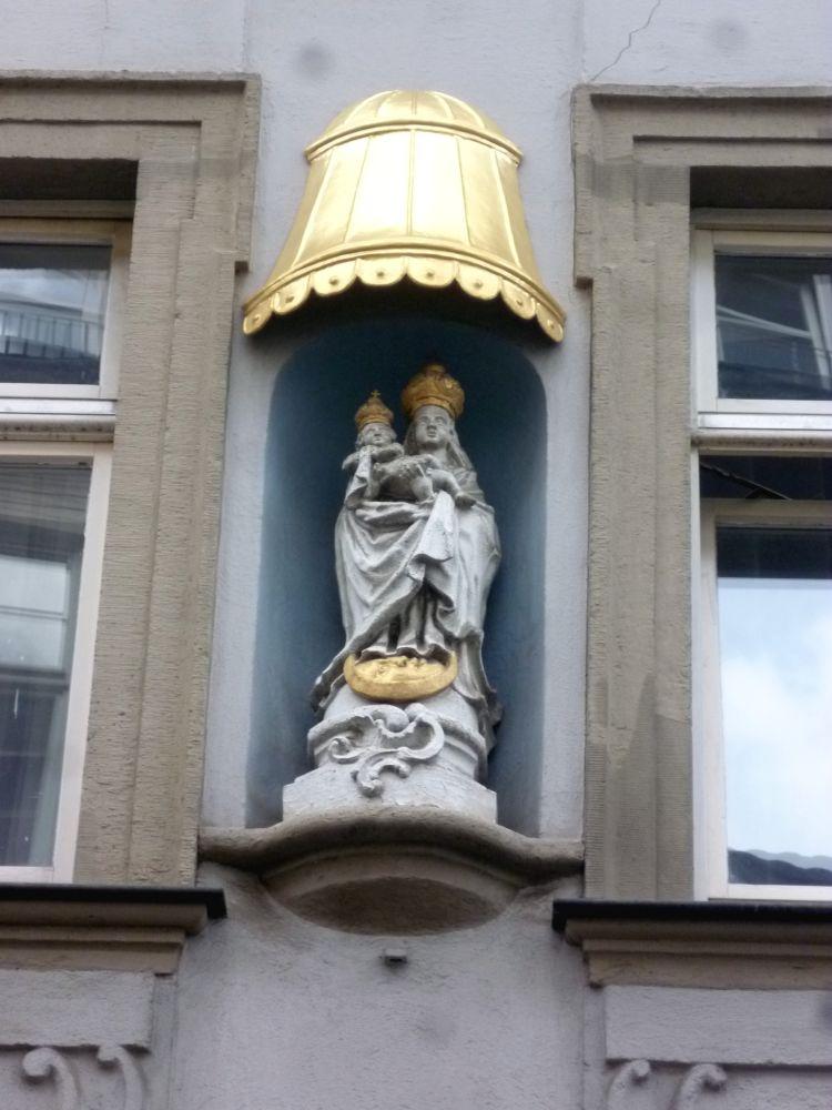 Eine Maire mit einem Kind auf dem Arm aus weisgrauem Sandstein. Die Figuren sind in edlen langengewändern gekleidet. Beide Figuren tragen eine goldene Krone. Die Figur ist in eine Mauer eingelassen, und wird von einem goldenen Dach geschützt.