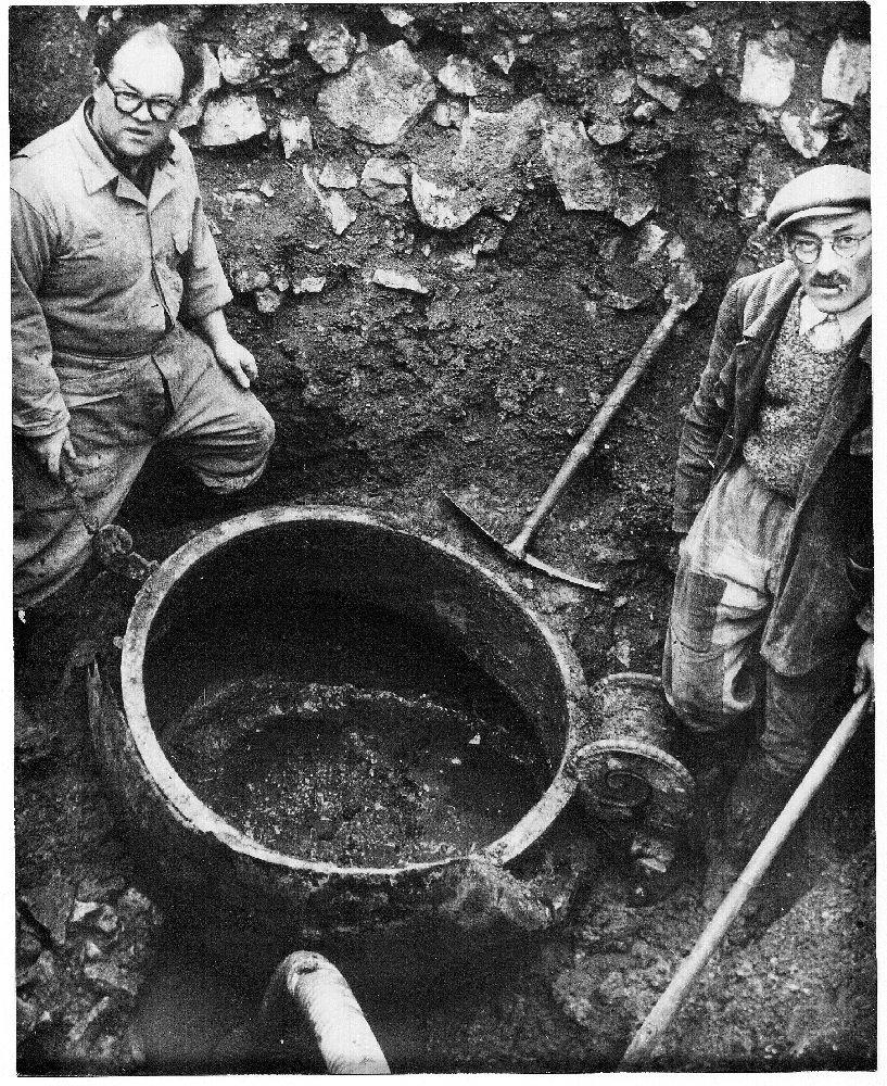 Die entdeckung des Grabes der rinzessin von Vix. Zwei männer stehen neben dem Krater, der halb ausgegraben ist.
