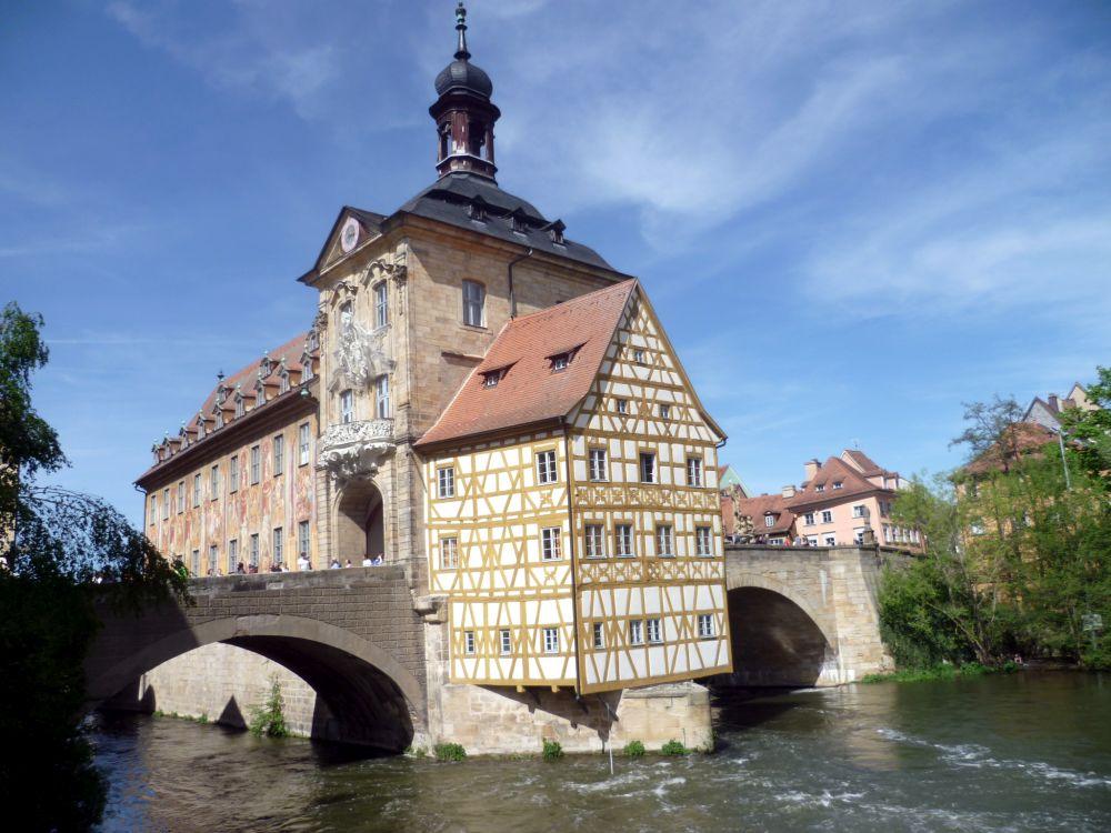 Das Rathaus in Bamberg in der Regnitz. Das Rauhaus steht af einer Insel im Flus und ist Links und Rechts mit steinbrücken mit dem Festland verbunden. Das Rathhaus hat einen Turm in der mitte, der auf der Brücke steht, und der stark mit figuren verziert ist.. Im Vordergrund ist ein Fachwerkanbau zu sehen, der zum Teil über dem Fluss zu schweben schein. Im Hintergrund ist ein weiterer anbau zu sehen, der mitten im Fluss steht, und der Bunt bemalt ist.