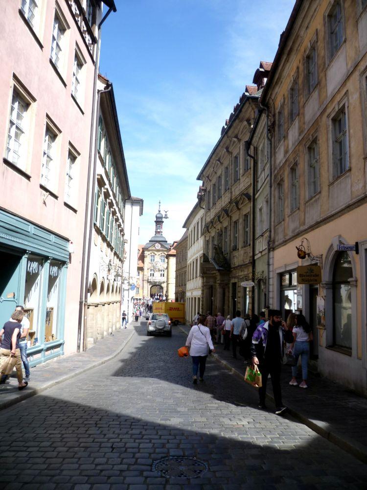 Blick durch eine Strasse in Bamberg. Alte Häuser stehen links und rechts einer Gasse in die helles Sonnenlicht fällt. Viele Fusgänger und Fusgängerinnen laufen in der Gasse herum, am ende der Gasse ist ein edel gebäude mit einem Turm zu sehen.