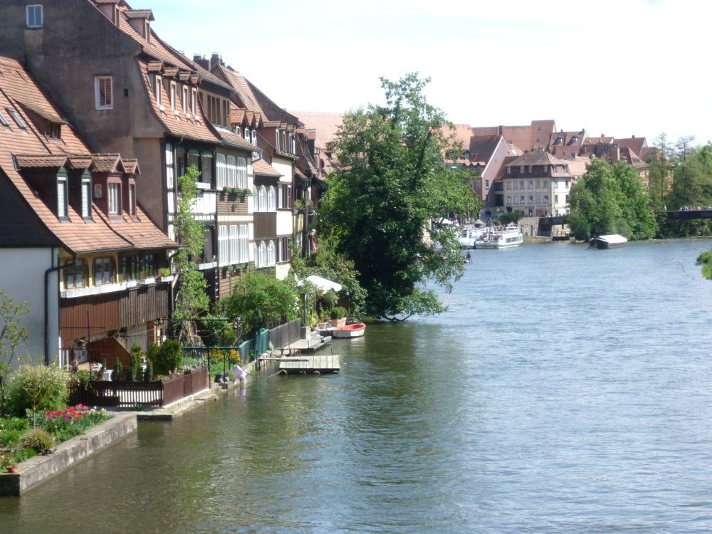 Häuser am Ufer der Regnitz. Es handelt sich um eine Häuserzeile mit zwei bis dreistöckiegen Altbauhäusern. Die Gebäude grenzen dierekt an das Flusufer an, und haben kleine Molen, die mit gartenzäunen umgeben sind, und als Gärten dienen.