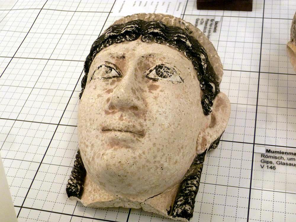 Eine Mumienmaske liegt auf Milimeterpapier. Sie besteht aus Gips und stammt aus dem Ähypten der römischen Zeit.