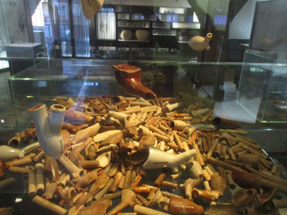 Ein haufen bestehend aus hunderten Bruchstücken von Tonpfeifen. Dadrüber sind eineige etwas besser erhaltene Tonpfeiffen aufgehangen.