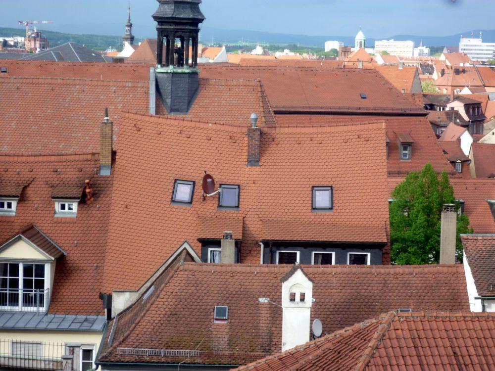 Ein Dächermeer aus rot gedeckten Ziegeldächern. Es handelt sich um die Dächer von Bamberg. Ein Dach fällt besonders auf, da der Dachbalken extrem druchhängt.