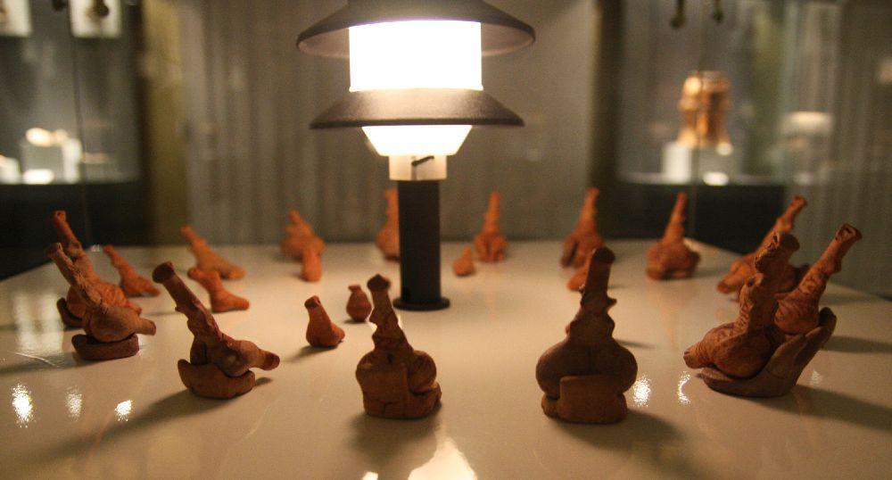 Unzählbar viele getöpferte Frauenfiguren sind im kreis um eine Gartenlampe herum arrangiert.