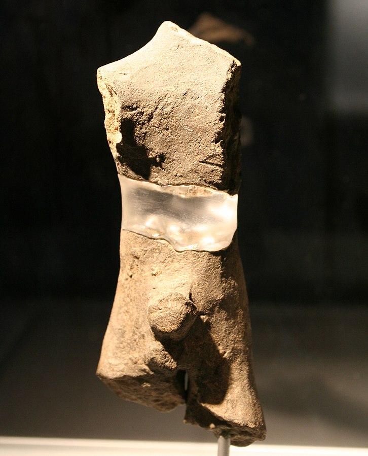 Jungsteinzeitliche Idolfigur. Ein errigierter Penis ist deutlich hervorgearbeitet, Kopf und Arme sind abgebrochen. Auch die Beine Fehlen zum teil. Die Figur ist getöpfert und in einerm hellen Grau-Braunton gemacht. Der Bauch wird von einem Klebestreifen zusammen gehalten.