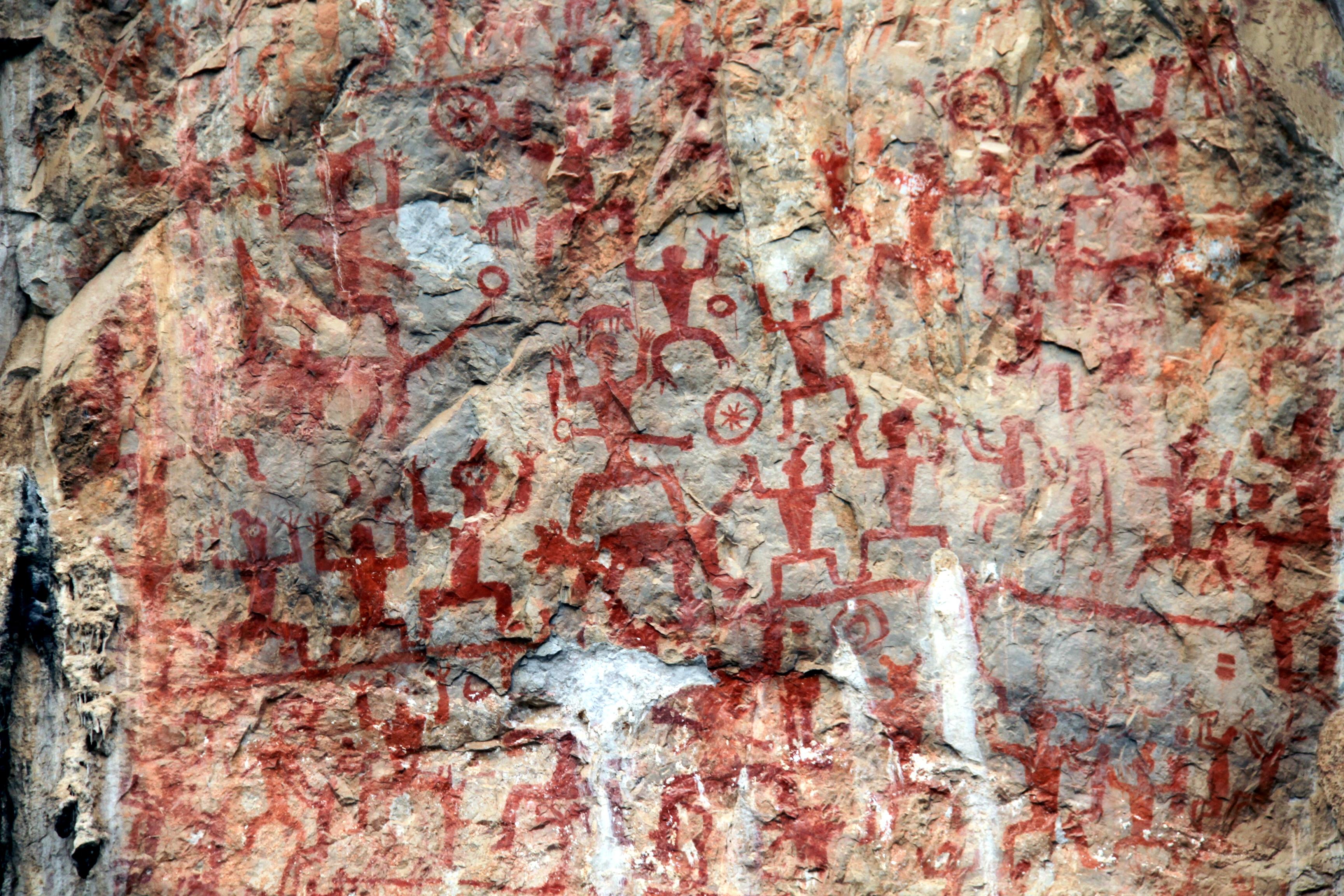 Felsbilder von Huashan in China. Eine Felswand die über und Über mit roten Figuren bemalt ist. Viele Strichmännchen ähnliche Zeichnungen sind dabei, die die Arme heben.