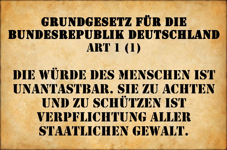 """Schrift vor einem Pergament: !Grundgesetz für die Bundesrepublik Deutschland Art. 1 (1) Die Würde des Menschen ist unantastbar. Sei zu achten und zu schützen ist verpflichtung aller staatlichen Gewalt."""""""
