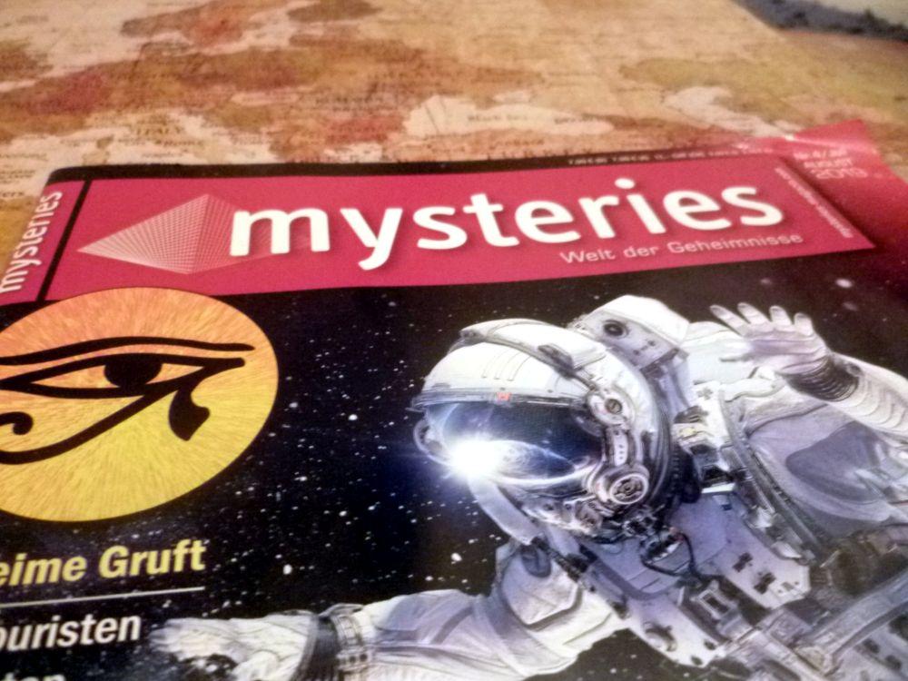 Die Zeitschrift Mysteries liegt zugeschlagn auf einer Weltkarte. Nur der Obere Teil der Zeitschrift ist zu sehen.