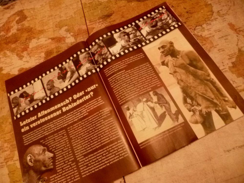 Die Aufgeschlagene Zeitrschrift Mysteries liegt auf einer Weltkarte. Die Zeitschrift ist nicht zu lesen, aber die Bilder sind zu sehen. Sie zeigen schwarzweisfotos eines behinderten Mannes.