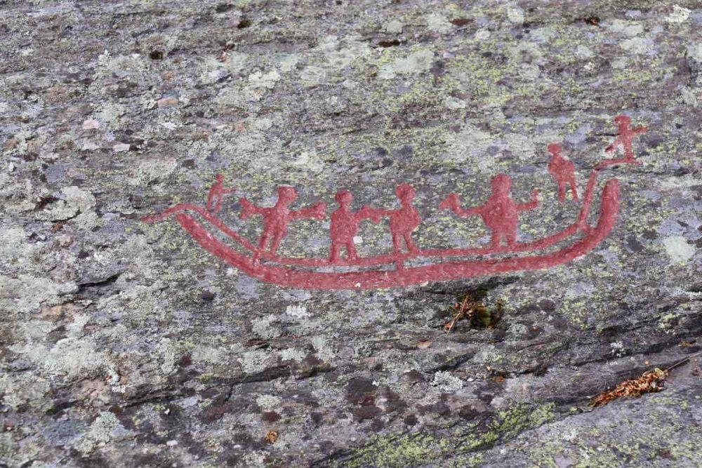 Ausschnitt aus den Felsritzungen von Tanumshede in Schweden. 6 Figuren befinden sich auf einem Schiff das als gebogene doppelline Dargestellt ist. Eine Figur steht neben dem Schiff. Es handelt sich um eine Rot ausgemalte ritzung auf einem grauen Fels. Die Figuren sind Strichmänchenartig gezeichnet mit rundlichen Bäuchen. Sie haben die Arme erhoben.
