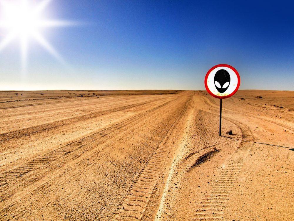Wüste in Praller sonne mit Reifenabrücken. Ein Warnschild mit einem Alien ist neben den Reifenspuren aufgestellt.