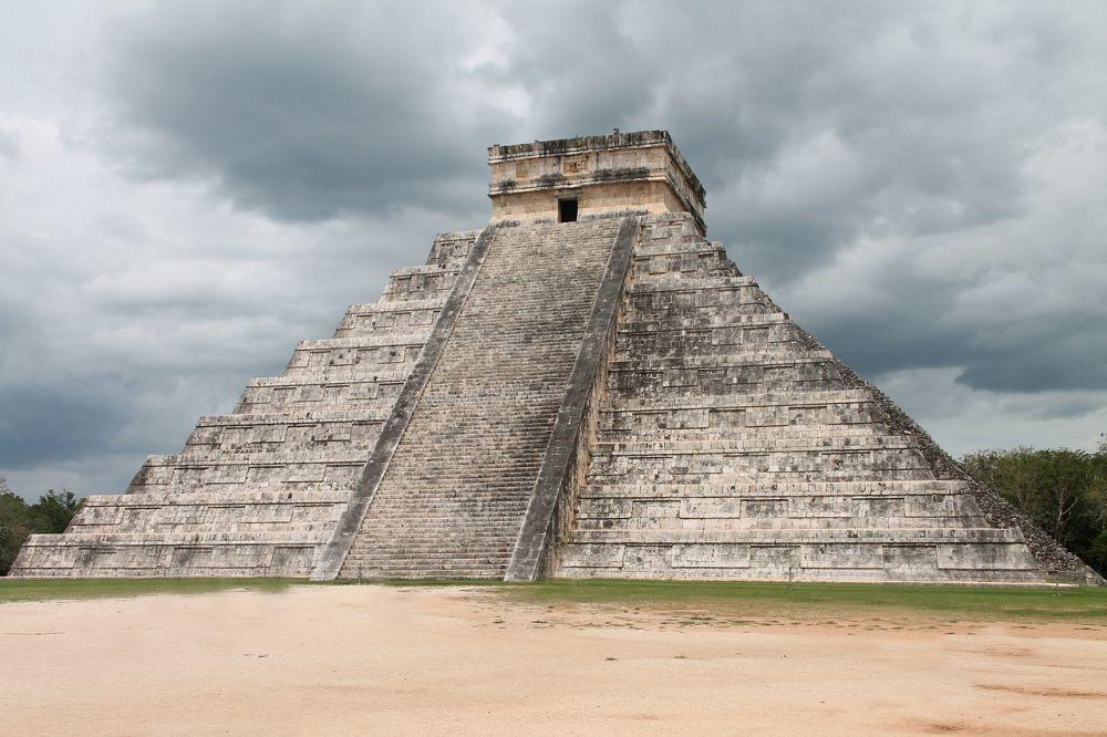 Eine Mayapyramide vor einem grauen bewölkten Himmel.