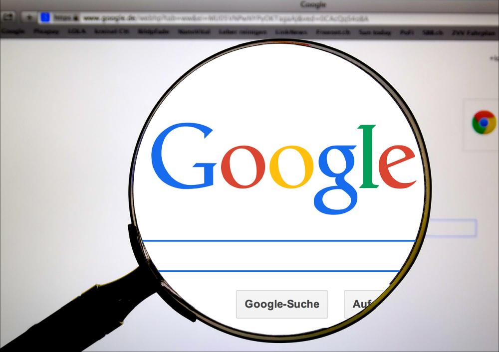Bild von der Googlestartseite. Davor ist eine Lupe plaziert die das Googleloge vergrößert.