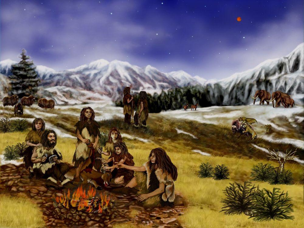 Steinzeitgruppe in einer Hügellandschaft vor einem Alpenpanorama. vereinzelt liegt schnee. Im hintergrund sind zwei Mammuts und weitere Tiere und Menschen zu sehen. Im vordergrund sitzen 6 Menschen um ein Lagerfeuer. Sie tragen Kleidung aus fell.
