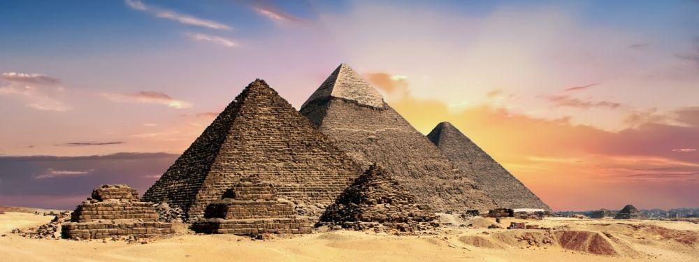 Die Pyramiden von Gizeh vor einem Sonnenaufgang.