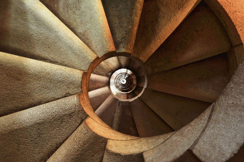 Ein Treppenhaus einer Wendeltreppe die sich nach untern schraubt.