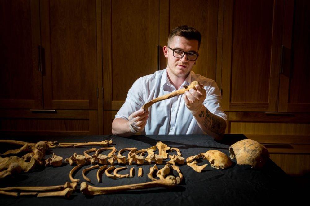 Ein Mann mit einer Brille und einem blauen Hemd sitzt an einem Schwarzen Tische auf dem ein Skelett ausgebreitet iat. Der Mann hält einen Oberarmknochen des Frauenskeletts aus dem Tower of London in der Hand.