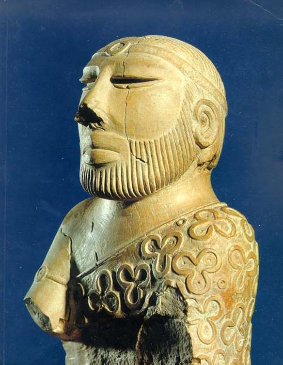 Eine Figur die einen Mann Zeigt. Er trägt ein geblümtes gewand, das nur über eine Schulter geht, und einen Bart. Um die Strin hat er eine art Diadem. Die Frisur ist kaum zu erkennen.