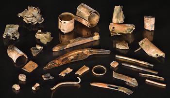 Viele Einzelteile. Ein Birkenrindengefäß und daneben liegt der ehemalige Inhalt. Viele nützliche Einzelteile wie ein Kamm aus Knochen, ein Knochenpfriem.