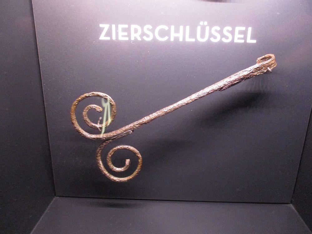 Ein Metallobjekt, dass vor der Überschrift Zierschlüssel aufgehangen ist. Es handelt sich um ein längliches schlüsselförmiges Objekt, dass keinen Bart hat. Am Griff sind zwei Zierspiralen angebracht.
