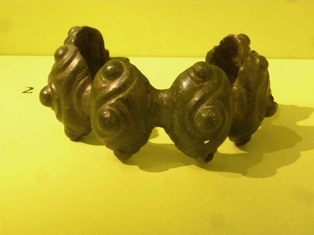 Ein Hohlbuckelring vor einem gelben Hintergrund. Der Armring ist hinten offen und besteht aus 6 halbugelförmiegen ausstülpungen die aneinander gereiht sind. Jede halbkugel ist mit Punkten und Spiralen verziert. Der Armring bestaht aus grünem Metall.