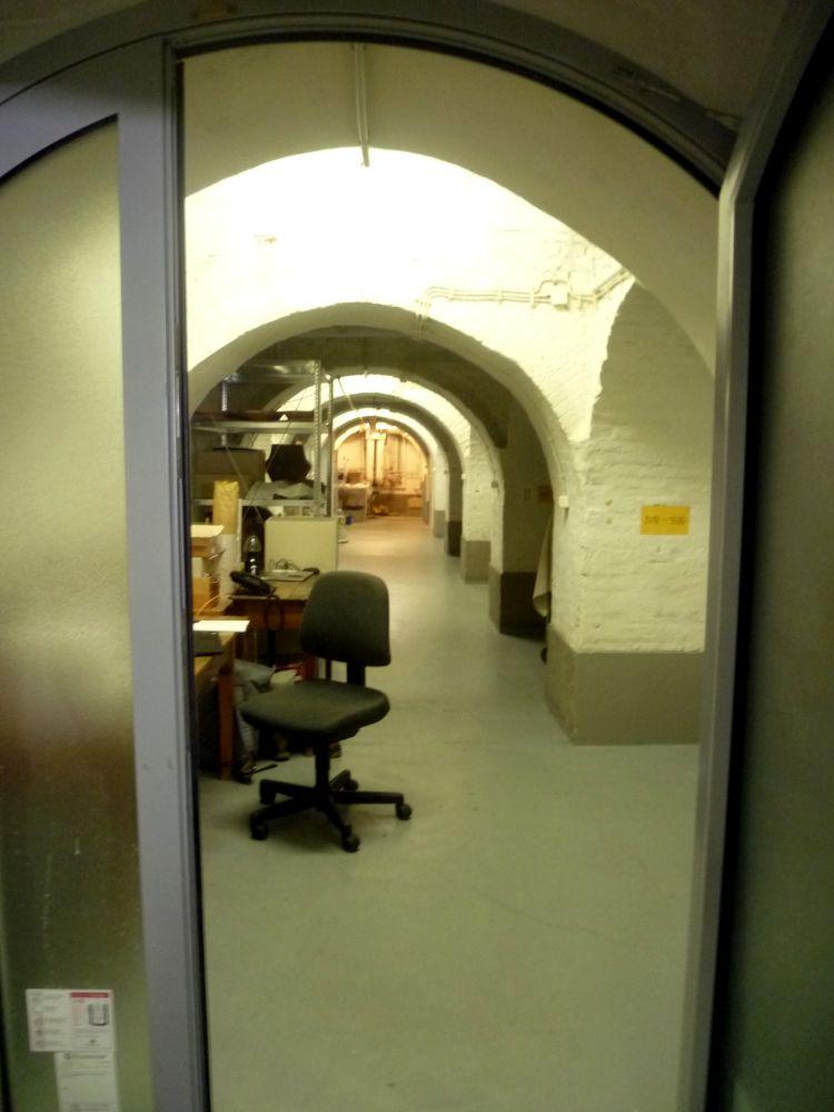 Ein Langer Kellerflur mit einem Stark gebogenen Gewölbe das weis gestrichen ist