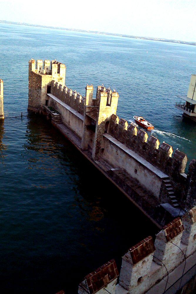 Die Hafenanlage von Sirmione ist mit einer Mauer geschützt die ins das stille Wasser des Sees hinein ragt. Diese Mauer ist mit Zinnen versehen die einzeln Dächer tragen. Es sind zwei Wehrtürme zu sehen, die ebenfalls mit Zinnen geschützt sind und die man über einen Wehrgang betreten kann..