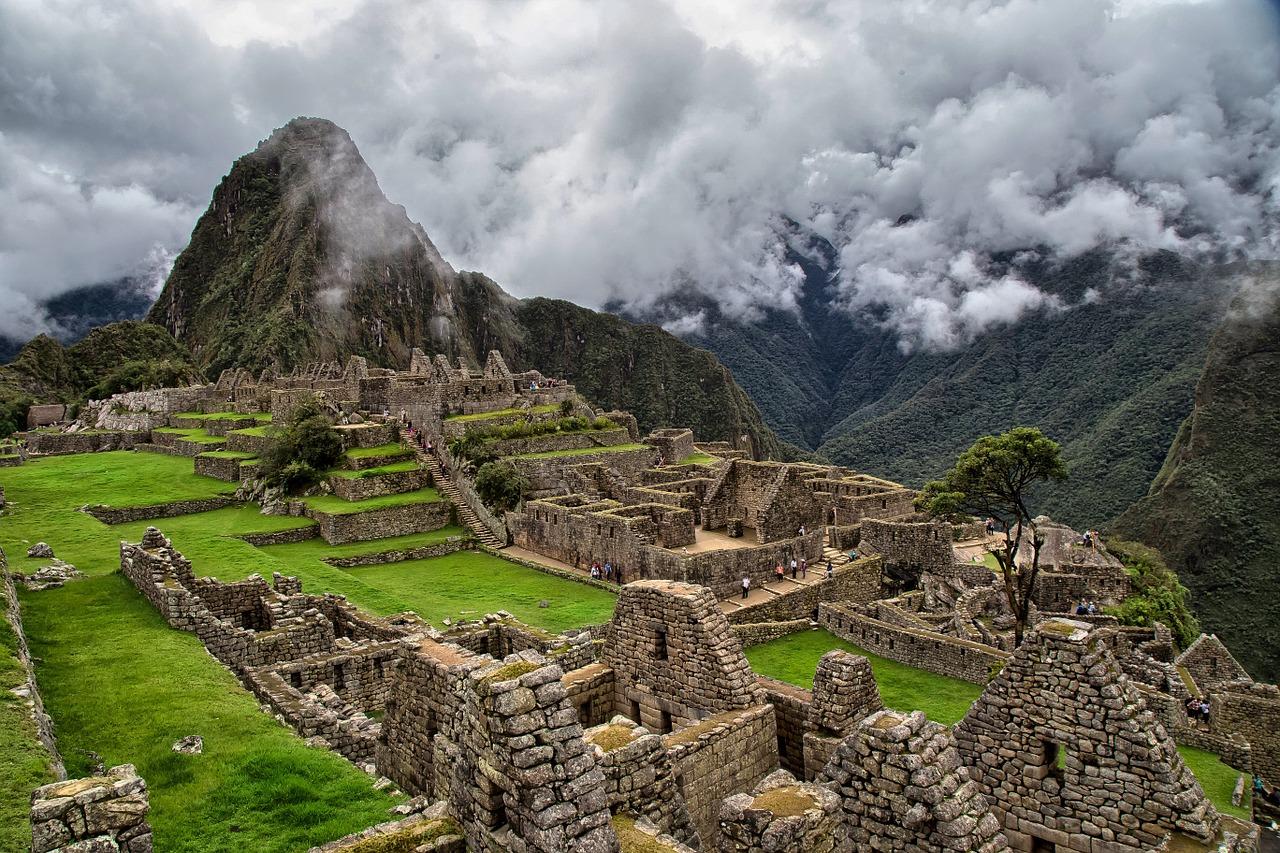Ein Stark bewölkter Himmel, der gegen einen Bergsport trifft, unter diesem Bergsporn liegen Ruinen von den Häussern des Machu Picchu. Die Giebelwände der einzelnen aus grauen Stein gemauerten Gebäude sind noch gut zu erkennen. Die Ruinen stehen auf einer saftig grünen Wiese und sind so hoch gelegen, dass auch sie fast an die Wolken anstossen.