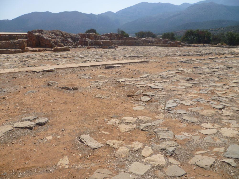 Im Hintergrund blaue Berge, im Vordergrund die Ruinen des Palastes von Malia. Die Ruienen sind leicht rötlich. Vor ihnen verläuft ein Gepflasterter weg, der leicht vergangen ist. Zwischen den Pflastersteinen liegt roter Sand.