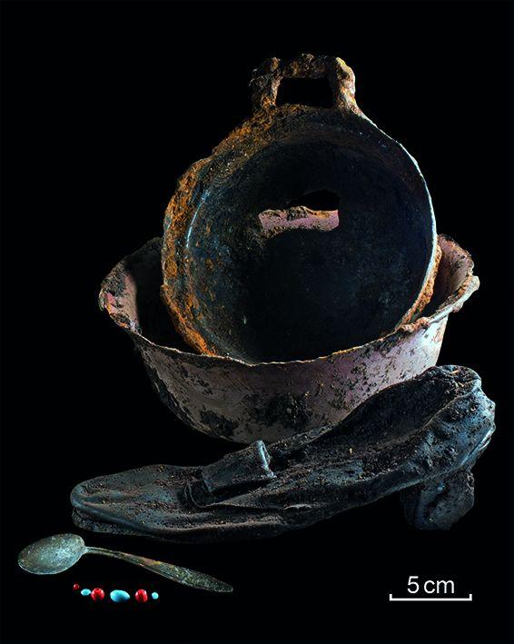 Gegenstände die auf einem Erschießungsplatz der Waffen-SS gefunden wurden vor einem schwarzen Hintergrund.