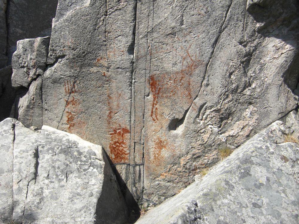 Eine graue Felswand mit roten Zeichnungen deutlich zu erkennen ist eine Art Hirsch