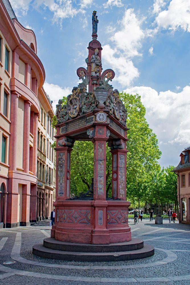 Der rote Marktbrunnen in Mainz. Es handelt sich um einen Runden Bau der mit einem kunstvoll verzierten Dach versehen ist. Obenauf thront eine Heiligenfigur.