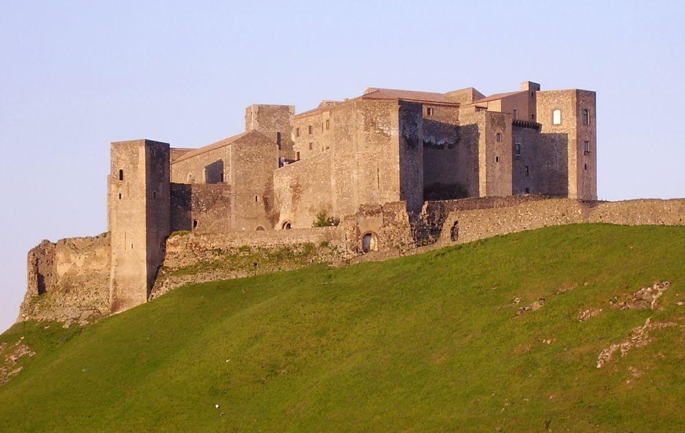 Ein roter Backsteinbau auf einem hohen grünen Hügel. Das Gebäude ist verwinkelt und hat viele Türme im mediterranen Stiel. Es handelt sich um das Kastell von Melfi.
