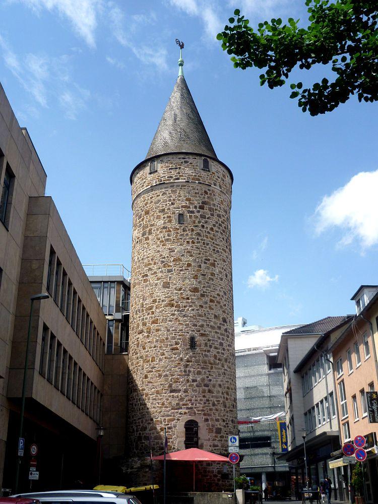 Ein Aus hellen Feldsteinen gemauertert Turm. Der Druselturm ist rund, und hat ein spitzes Dach, das mit schwarzen Schindeln gedeckt ist.