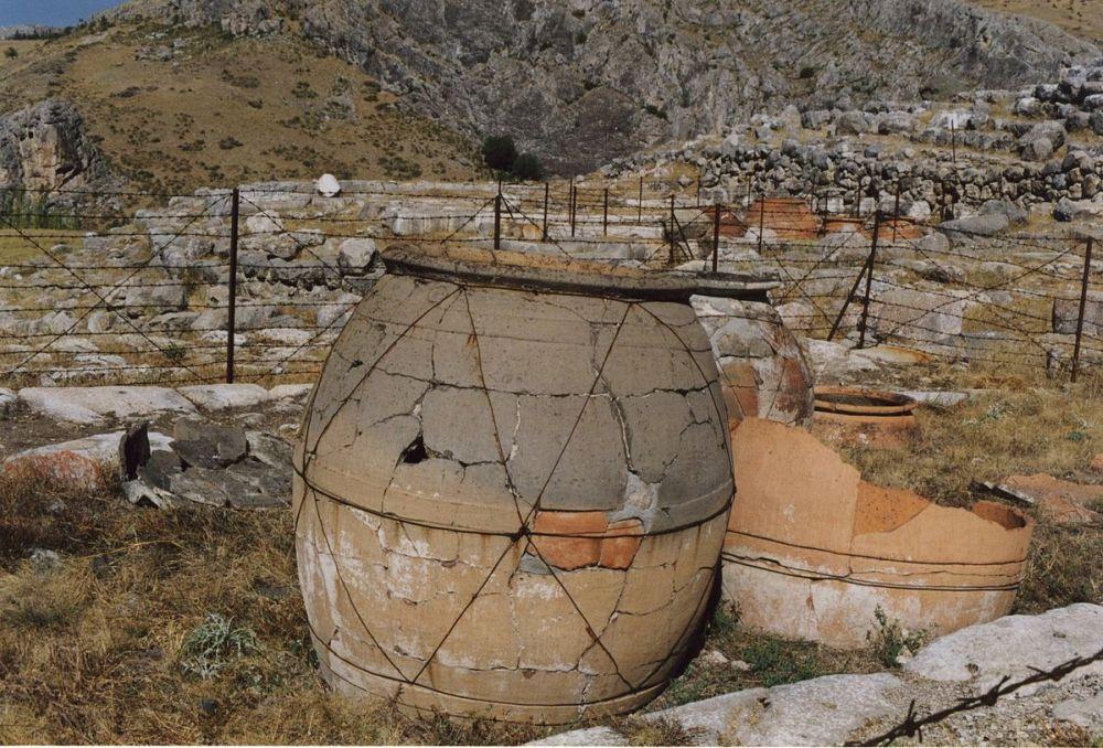 Ein Großes Geramikgefäß neben eineinm Zerscherbten auf einem Freien Feld. Auf dem Freien Feld sind viele Mauerzüge einer Archäologischen tätte zue rkennen. Es handelt sich um Hattusa in der Türkei.