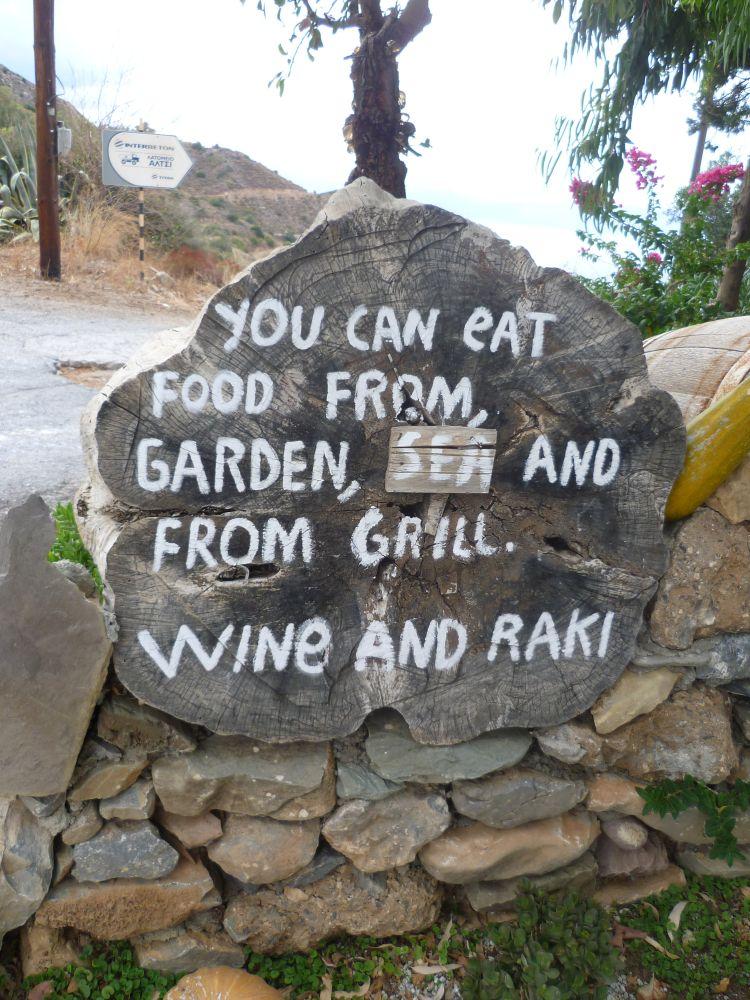 """Holzscheibe mit beschriftung. Mit Kreide staht dort geschrieben: """"You can eat food from, Gardan, Sea an From Grill. Wine and Raki"""