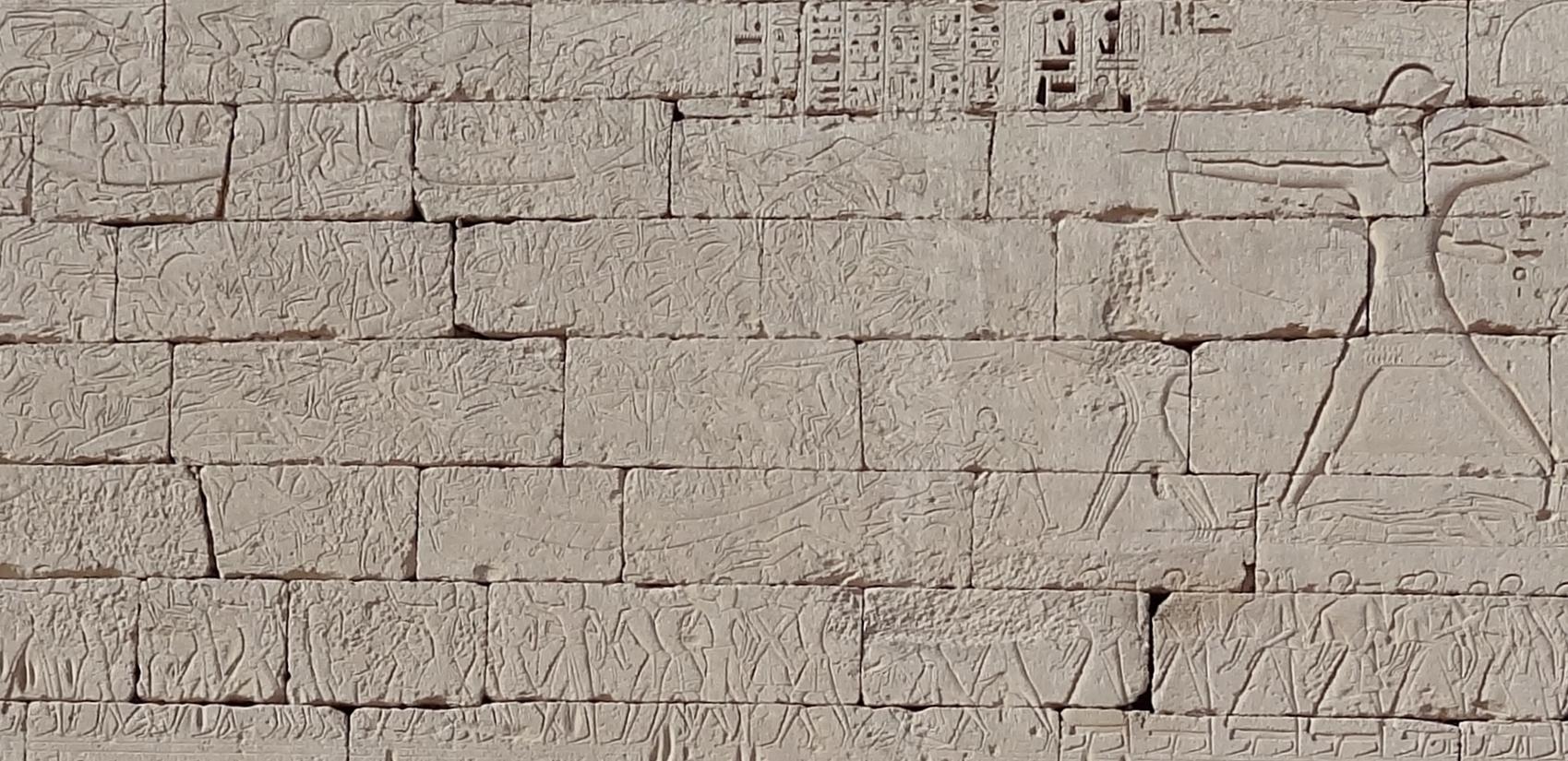 Eine Mauer aus Sandsteinblöcken, die mit einem Rilief versehen ist. Dargestellt ist eine Ägytisches Bil mit viele Menschen und einer großen Abbildung von Ramses III