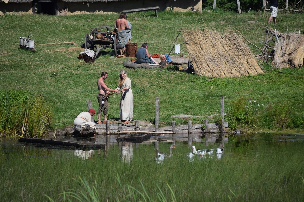 Foto einer Reenatcment Szene. 7 Menschen stellen das Leben der Wikinger, in Kostümen nach. Sie befinden sich auf einer Wiese an einem Uferrand.