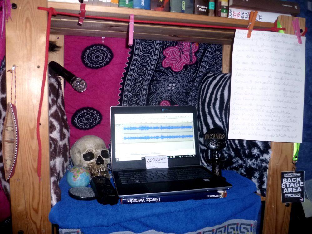 Ein Mikrofon, ein Laptop ein mobiles Aufnahmegerät, in einem Regalabteil, dass mit Handtüchern und Kissen ausgelegt ist und mit einem Spielzeuggkanu, einem Schädel, einer kleinen Weltkugel und weitern Objekten geschmückt ist.