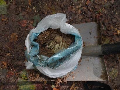 Eine Plastiktüte liegt auf einer Schaufel, in der Plastiktüte sind viele Münzen in situt zu sehen.